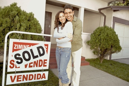 Happy Homeowners with Sold Sign